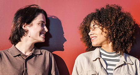 Two women smiling at each other while standing against a red wall in the sunlight