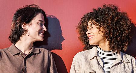 Due donne che si sorridono l'un l'altra in piedi davanti a un muro rosso sotto il sole