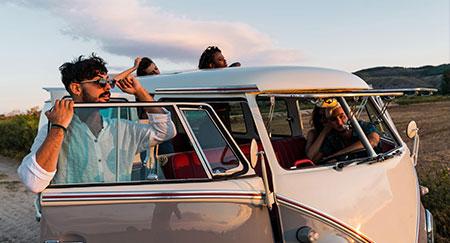 Jóvenes al lado de una furgoneta antigua que están mirando a lo lejos mientras viajan juntos en medio de la naturaleza