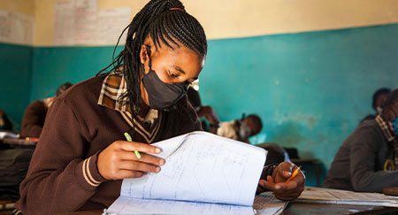 Uno studente, con una maschera facciale, frequenta le lezioni in una scuola di Lusaka, capitale dello Zambia