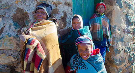 A Basotho family wrapped in blankets standing in front of door