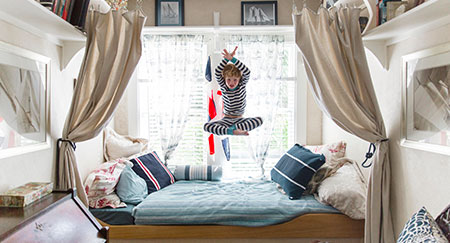 Male child jumping on bed