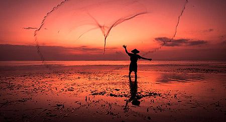 Fischer bei der Arbeit bei Sonnenaufgang