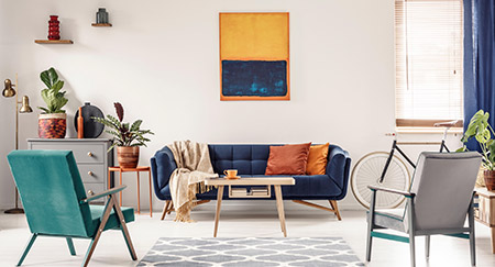 Real photo of a modern living room with a navy blue couch, two chairs, a bicycle, abstract artwork and indoor plants