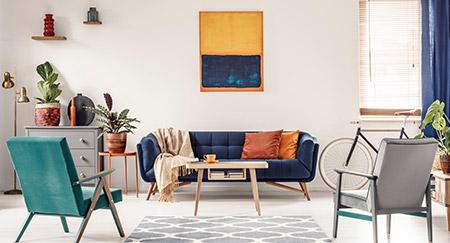 Foto vera di un soggiorno moderno con un divano blu navy, due sedie, una bicicletta, opere d'arte astratte e piante d'appartamento