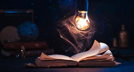 Stern in einer Glühbirne über einem aufgeschlagenen Buch
