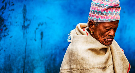 Old Nepalese man in hat in front of blue background