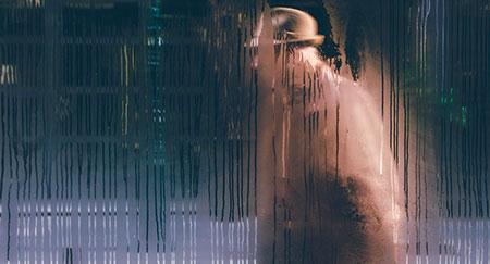 Blick auf Mann mit Hut durch ein nasses Fenster