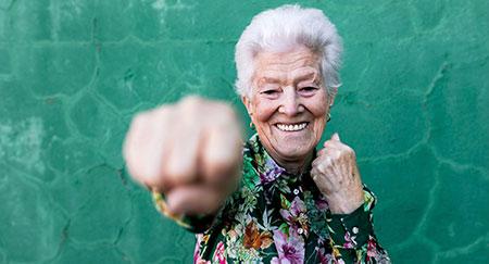Fröhliche ältere Dame in eleganter, bunter Bluse beim Boxen in die Kamera vor einer grünen Wand