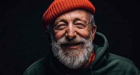 Primer plano del retrato de un hombre feliz de 70 años que dibuja una sonrisa en su cara llena de arrugas, y lleva un sombrero juvenil naranja y una sudadera con capucha verde, aislado sobre un fondo negro
