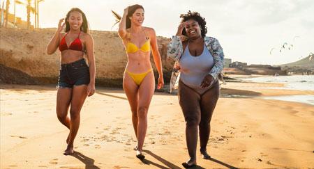 Glückliche Frauen verschiedener Herkunftsländer mit unterschiedlichen Körperformen beim Spazieren am Strand im Sommer