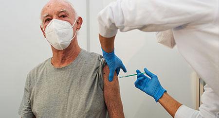 Un operatore sanitario inietta il vaccino Pfizer-BioNTech contro il COVID-19 ad un anziano in Germania