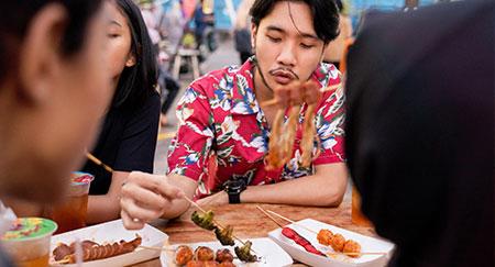 Gruppe junger Freunde beim gemeinsamen Genießen einer Mahlzeit im Freien.