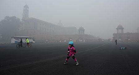 Bambini che pattinano immersi nello smog vicino alla residenza del presidente a Nuova Delhi.