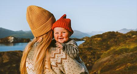 Madre con bambino in braccio che cammina all'aperto