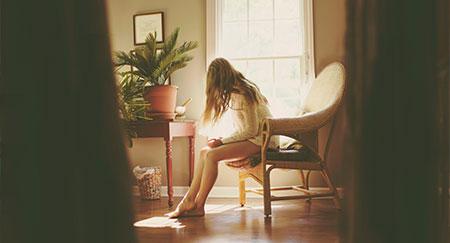 Giovane donna seduta su una sedia in soggiorno con una composizione cinematografica.