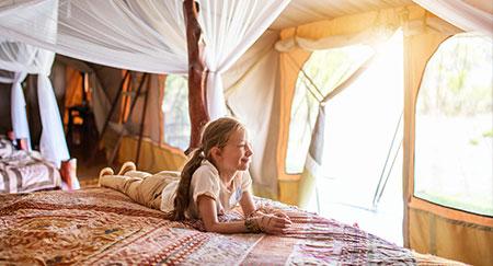Giovane ragazza in tenda da safari che si diverte durante le vacanze in Africa.