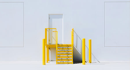 Una escalera color amarillo vivo y un muro blanco