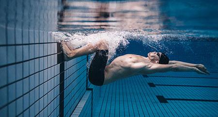 Giovane nuotatore che effettua una manovra in piscina.