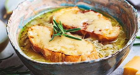 Zuppa di cipolle tradizionale francese con baguette e formaggio in tazza di ceramica