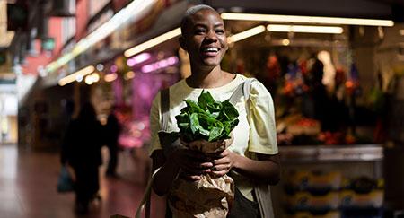 Ritratto di donna felice con borsa di carta in un mercato.