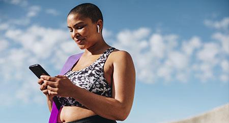 Donna in abbigliamento sportivo che controlla i suoi progressi di fitness sullo smartphone dopo una sessione di allenamento.