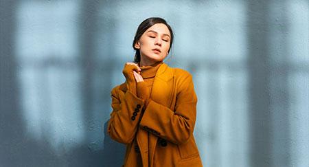 Mujer con los ojos cerrados que lleva un abrigo de invierno amarillo y se apoya contra una pared gris azulado