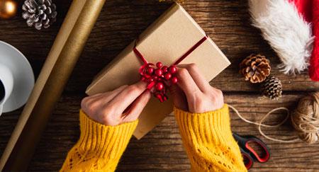 Hände beim Einpacken von Weihnachtsgeschenken