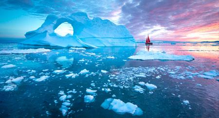 Kleines rotes Segelboot zwischen schwimmenden Eisbergen im Diskobucht-Gletscher während der Mitternachtssonnensaison des Polarsommers in Ilulissat, Grönland