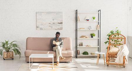 Älterer afroamerikanischer Mann beim Lesen eines Buches auf einem Sofa im Wohnzimmer