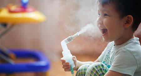 Giovane ragazzo usa il nebulizzatore a casa per la cura della bronchite.