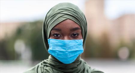 Portrait einer dunkelhäutigen muslimischen Frau mit blauer medizinischer Gesichtsschutzmaske im Freien