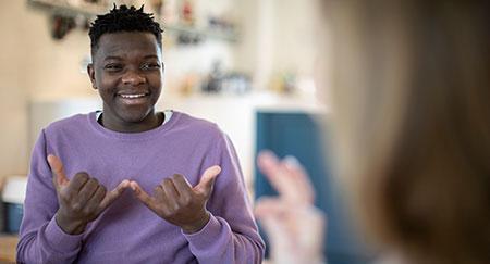 Ragazzo e ragazza conversano usando la lingua dei segni.