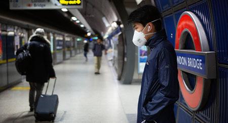 Trabajadores con mascarillas desplazándose al trabajo en el metro de Londres durante el brote de COVID-19.