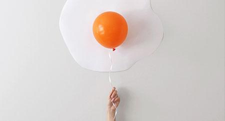 Frau mit Ballon vor einer Wand zum Schaffen der Illusion eines Spiegeleis