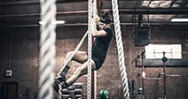 Young woman climbing rope in gym Stock Photo