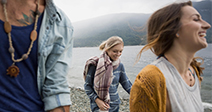 Young friends walking at lakeside - Stock Photo