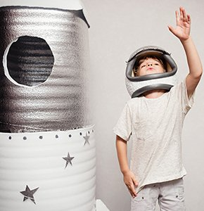 Happy child dressed in an astronaut costume playing with hand ma -  Stockfoto
