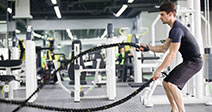 Young man exercising with battling rope at gym Stock Photo