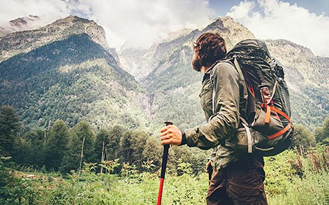 Man explorer with backpack hiking Travel Lifestyle concept beautiful mountains landscape on background adventure - Stock Photo