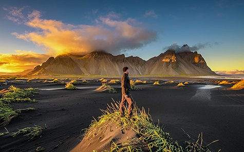 Hiker enjoying sunset at  Vestrahorn (Batman Mountain) and its black sand beach in Iceland - Stock Photo