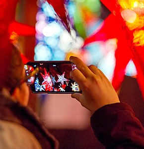 A tourist takes a picture of Christmas lanterns at a stall in the Edinburgh Christmas market. Stock Photo