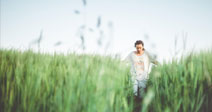 Man walking through green field - Stock Photo