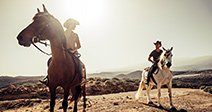 couple of horses and cowboys male and female ride free in the nature at the mountains in tenerife. lifestyle and alternative works or leisure activity Stock Photo